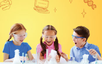 2 girls and a boy laughing and playing with test tubes.  smoke coming out of 3 beakers