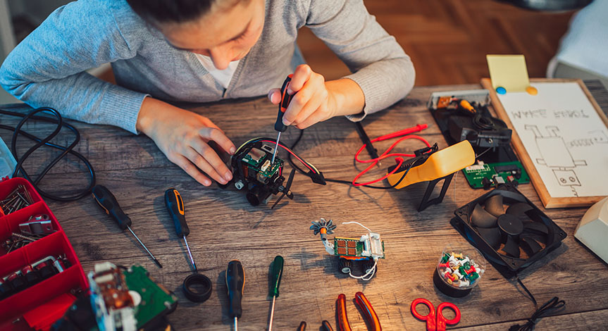 Girl constructs robotic toy. Robotic toy on a wood table full of tools