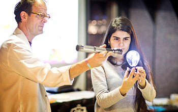 Mad scientist holding flash light point it at a light bulb that a girl is holding