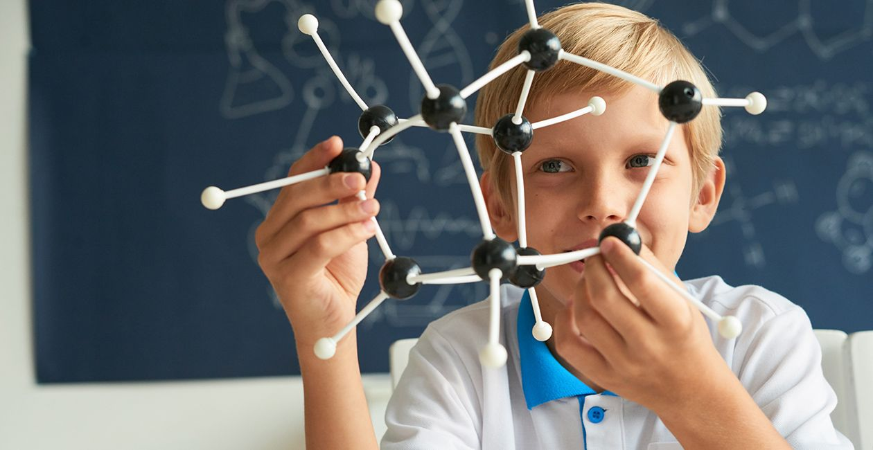 Boy looking at model to learn molecular structure.