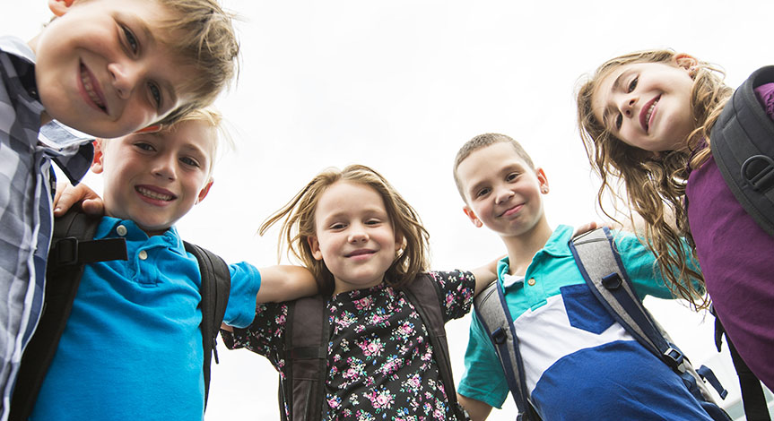 Kids looking down with arms around each all wearing school bags