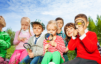 Kids sitting in a field while 3 of them are looking through a magnifying glass