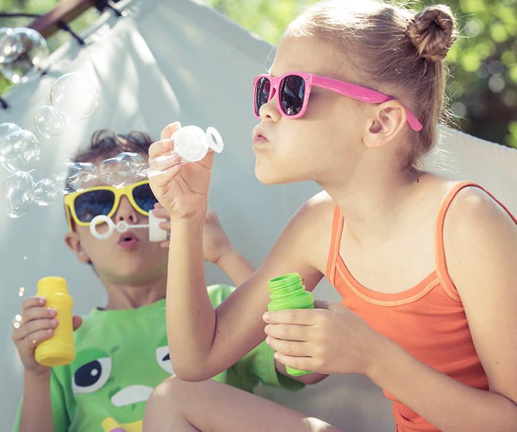 Two happy children wearing sunglasses lie on a hammock and play with soap bubbles