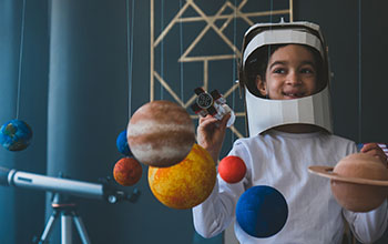 boy wearing cardboard astronaut helmet flying toy rocket through planets, cardboard spaceship rocket in the background