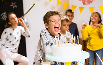 Little boy having fun on his birthday celebration holding a cake with 7 candles on it